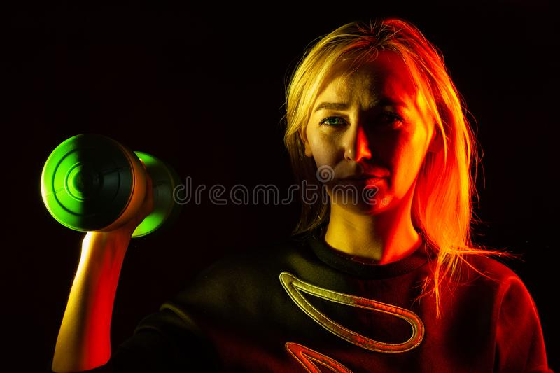 A young beautiful blonde woman in a black sweatshirt is holding a green plastic dumbbell in her hand raising up with backlight in royalty free stock photo