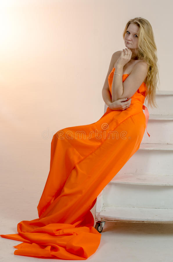 Young beautiful blonde woman in a bright orange fabric in a dress.  stock image