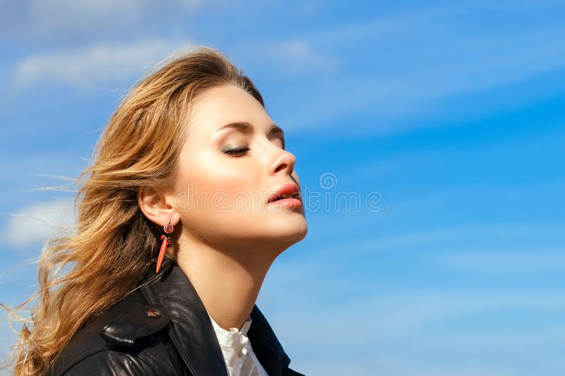 Young beautiful blonde closed her eyes against bright blue sky stock photography