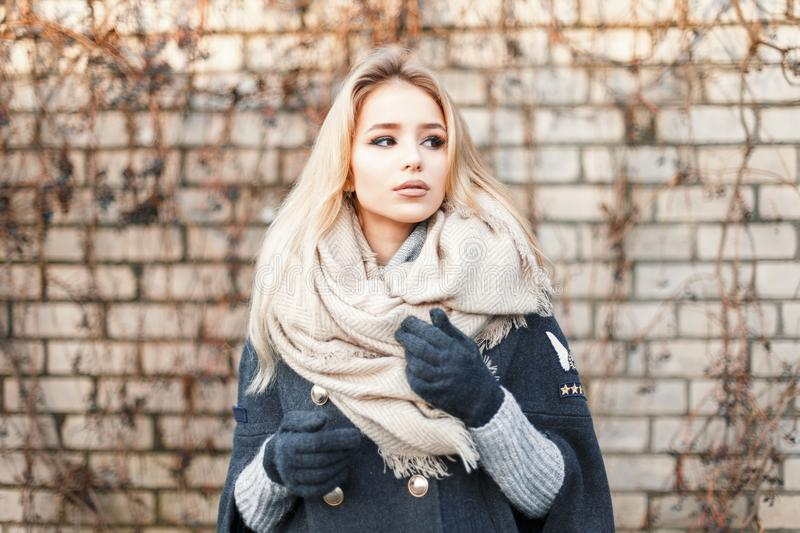 Young beautiful blonde woman with fashionable warm scarf near stock photos