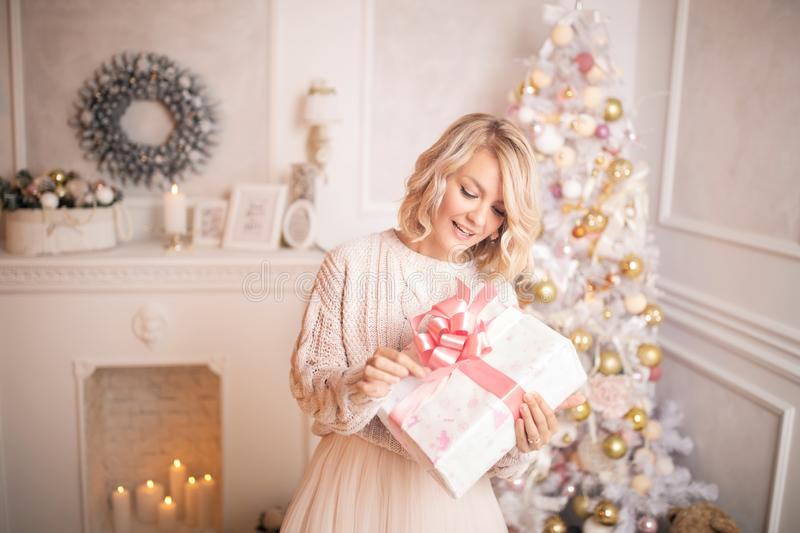 Young beautiful blonde woman holding a gift box. Christmas and new year concept. Studio shot royalty free stock images