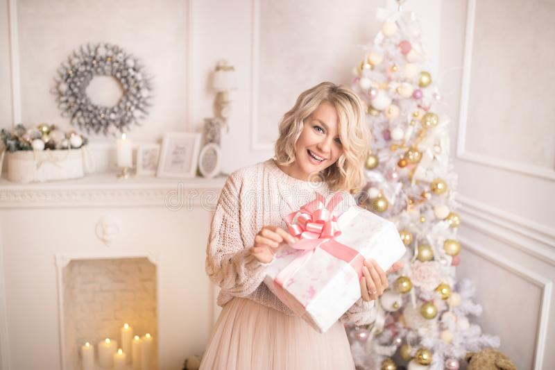 Young beautiful blonde woman holding a gift box. Christmas and new year concept. Studio shot royalty free stock photos
