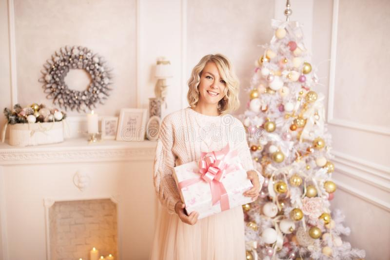 Young beautiful blonde woman holding a gift box. Christmas and new year concept. Studio shot stock images