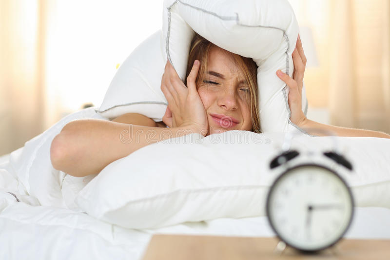 Young beautiful blonde woman lying in bed suffering from alarm c. Lock sound covering head and ears with pillow making unpleasant face. Early wake up, not royalty free stock image