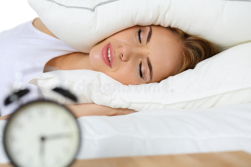 Young beautiful blonde woman lying in bed suffering from alarm c. Lock sound covering head and ears with pillow making unpleasant face. Early wake up, not royalty free stock photography