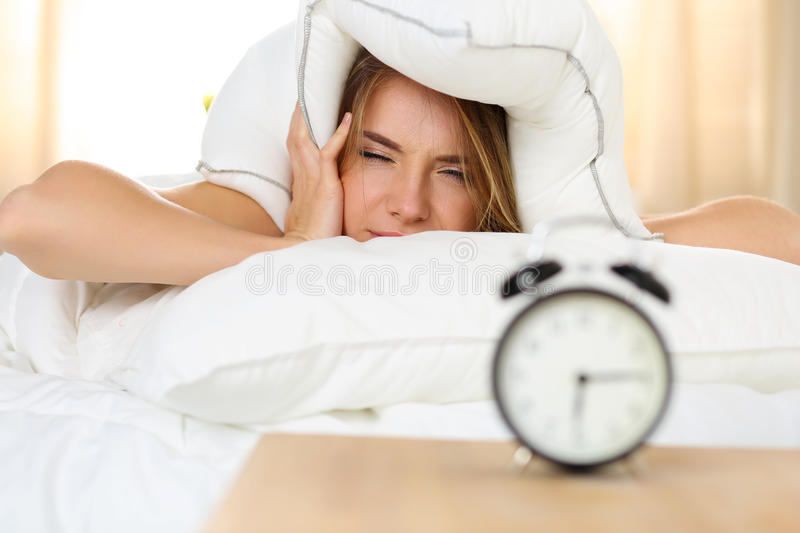 Young beautiful blonde woman lying in bed suffering from alarm c. Lock sound covering head and ears with pillow making unpleasant face. Early wake up, not royalty free stock images
