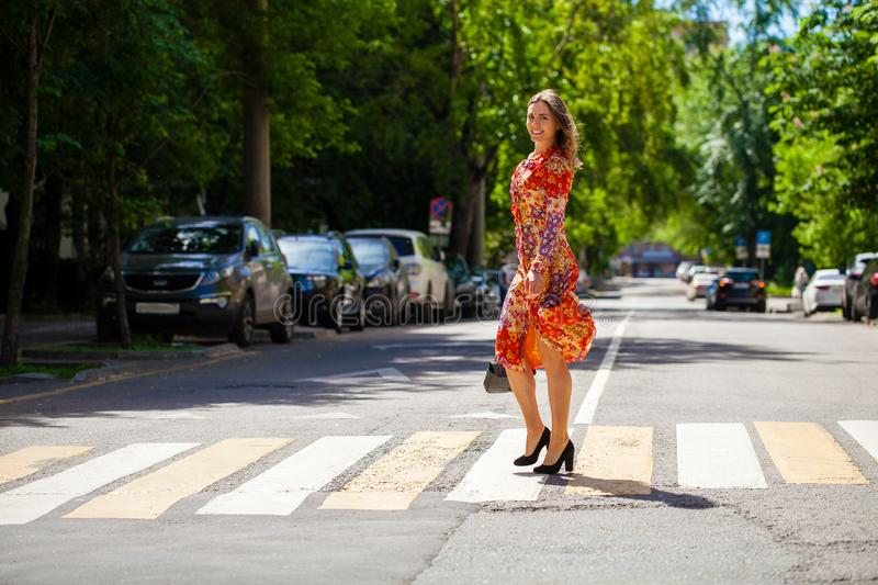 Young beautiful blonde woman in a red flower dress crosses the road at a crosswalk royalty free stock images