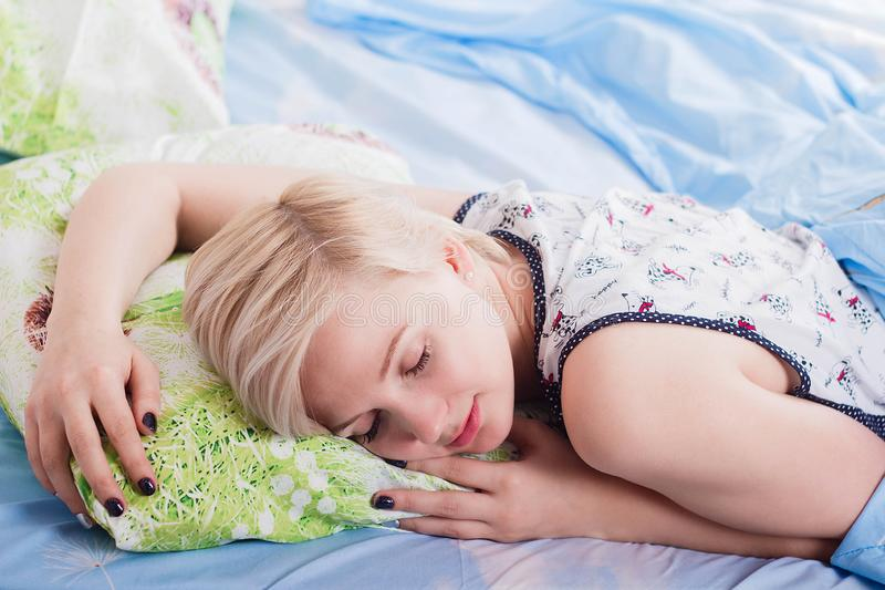 Young beautiful blonde woman sleeping in her bed in the morning royalty free stock image