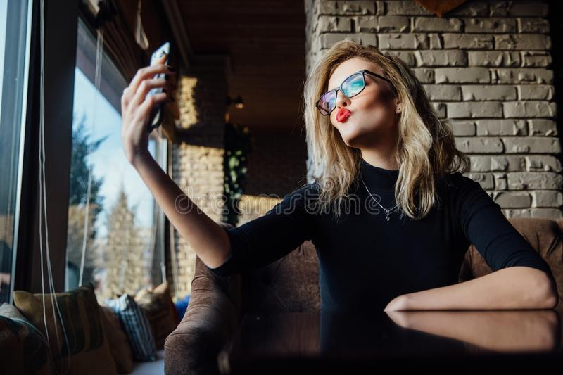 Young beautiful blonde woman taking a selfie in coffee shop. Hipster, red lips, glasses. stock images