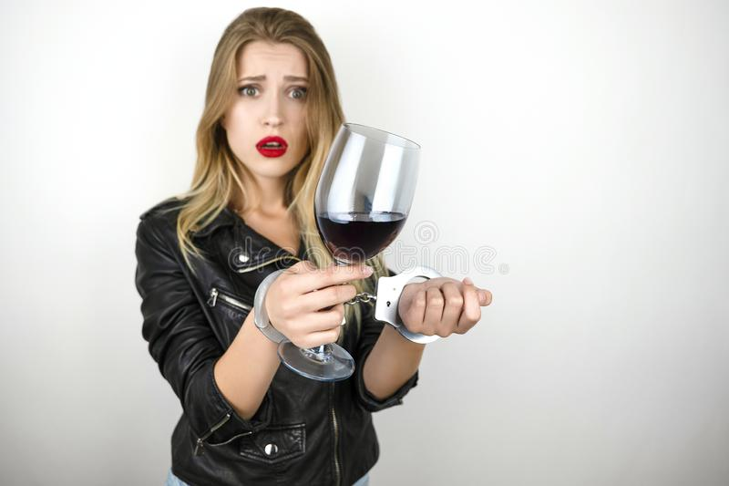 Young beautiful blonde woman wearing black leather jacket drinks wine and being arrested and handcuffed on isolated stock images