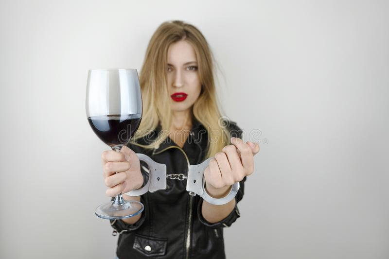 Young beautiful blonde woman wearing black leather jacket drinks wine and shows handcuffed arms on isolated white stock photo