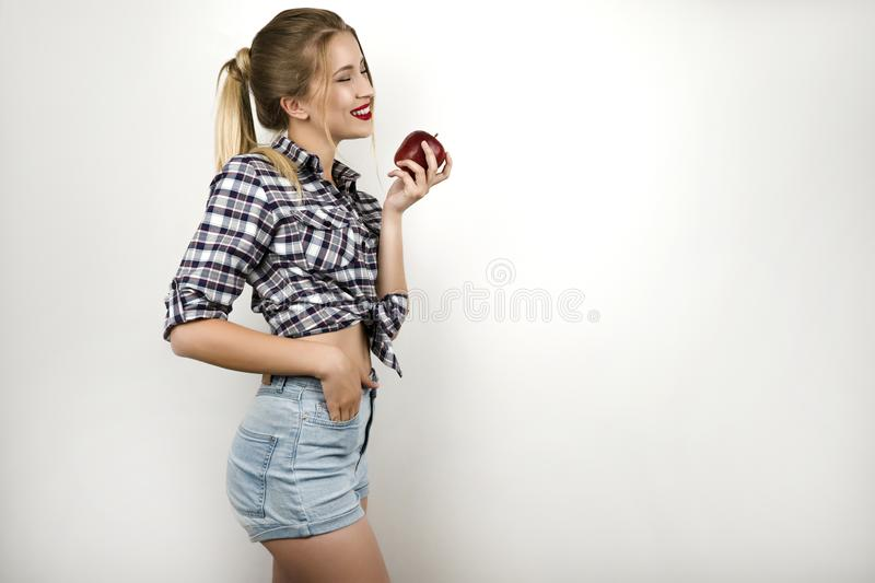 Young beautiful blonde woman wearing trendy checkered shirt and denim shorts holding fresh red apple isolated white stock photography