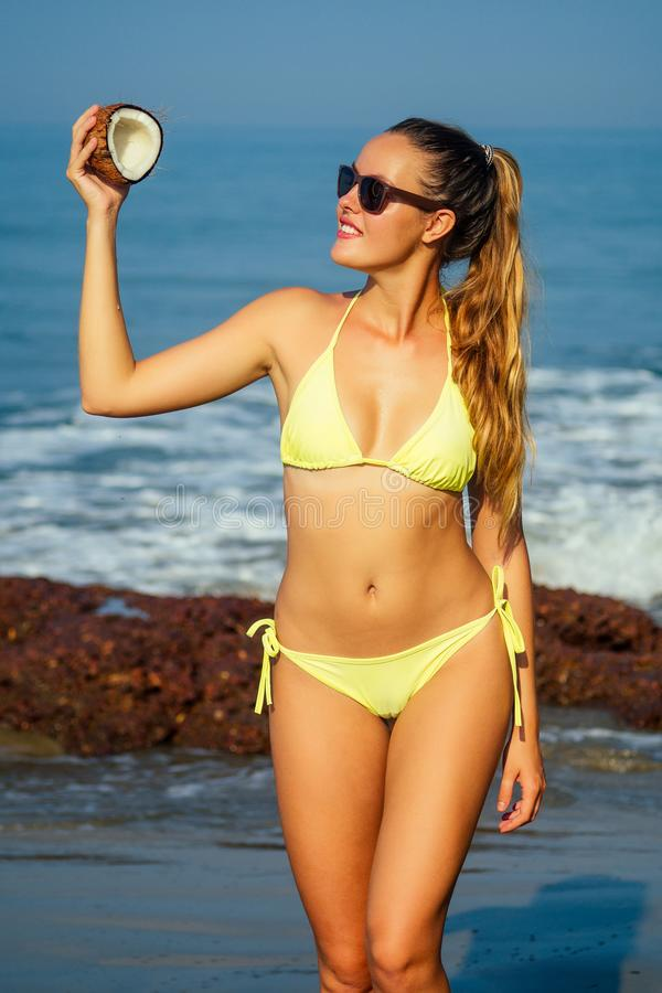 Young and beautiful blonde woman in a yellow swimsuit holding a coconut in her hand on a tropical beach.girl in bikini royalty free stock images