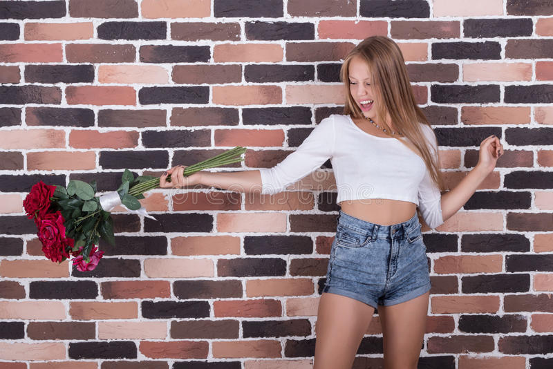 Young beautiful blong girl throws roses out stock image