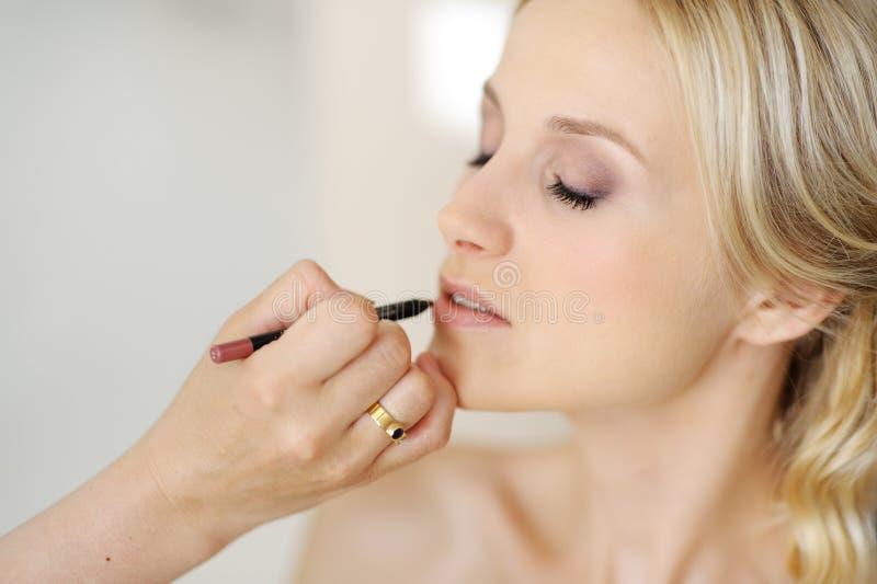 Young beautiful bride applying wedding make-up royalty free stock image