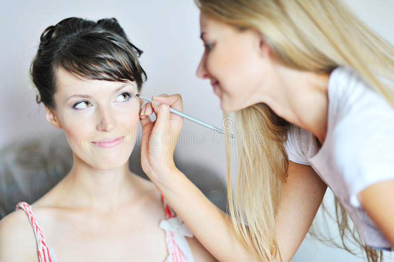 Young beautiful bride applying wedding make-up. By make-up artist royalty free stock photos