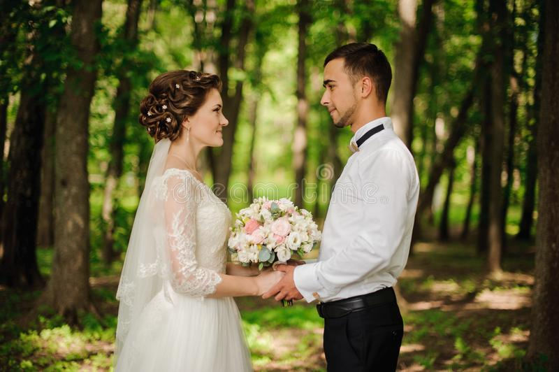 Young and beautiful bride and bridegroom holding one another hands stock photos