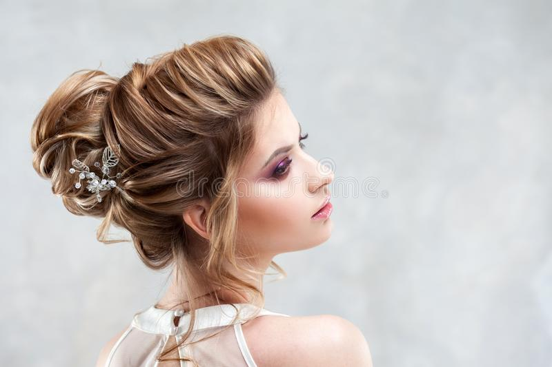 Young beautiful bride with an elegant high hairdo. Wedding hairstyle with the accessory in her hair stock photos
