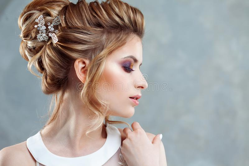 Young beautiful bride with an elegant high hairdo. Wedding hairstyle with the accessory in her hair. Close-up portrait on light background royalty free stock photo