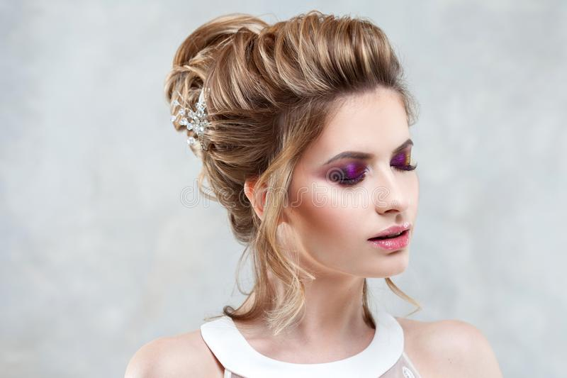 Young beautiful bride with an elegant high hairdo. Wedding hairstyle with the accessory in her hair royalty free stock image
