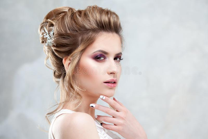 Young beautiful bride with an elegant high hairdo. Wedding hairstyle with the accessory in her hair. Close-up portrait on light background stock photos