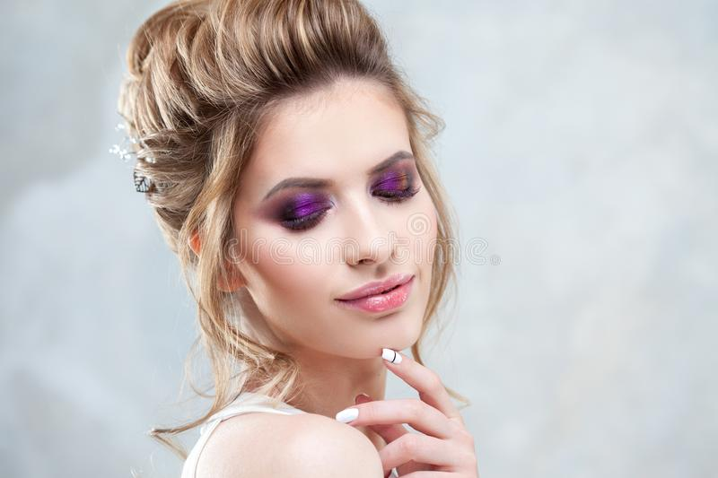 Young beautiful bride with an elegant high hairdo. Wedding hairstyle with the accessory in her hair stock photo