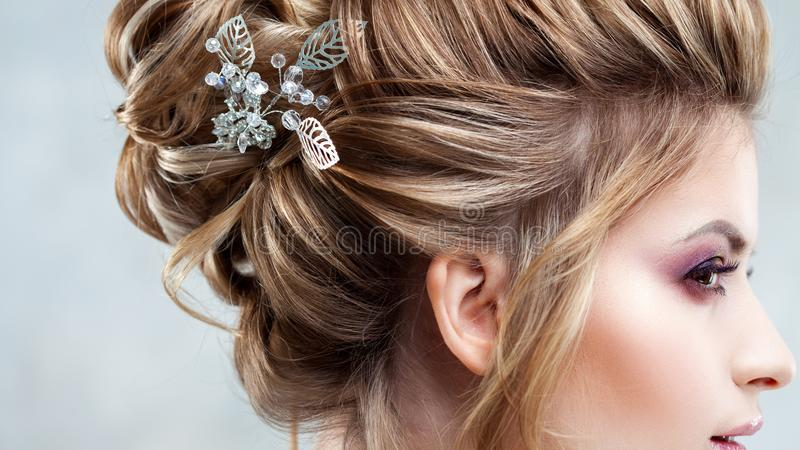 Young beautiful bride with an elegant high hairdo. Wedding hairstyle with the accessory in her hair stock photography