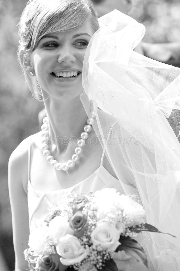 Young beautiful bride with flowers outdoor stock photo