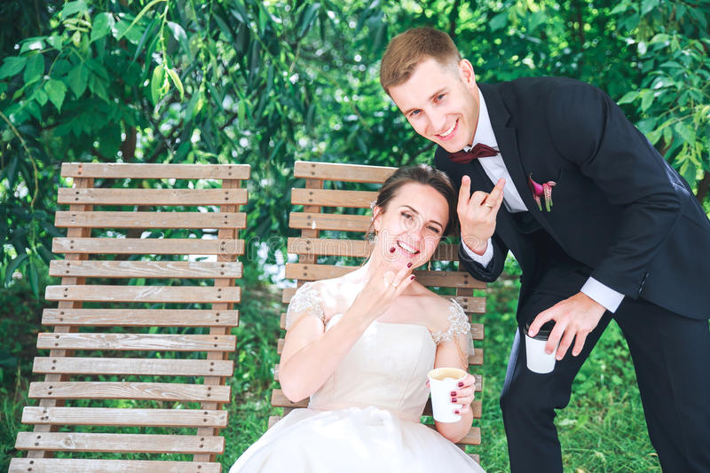 Young beautiful bride and groom drinking coffee at the outdoors cafe . Happy wedding day royalty free stock photography