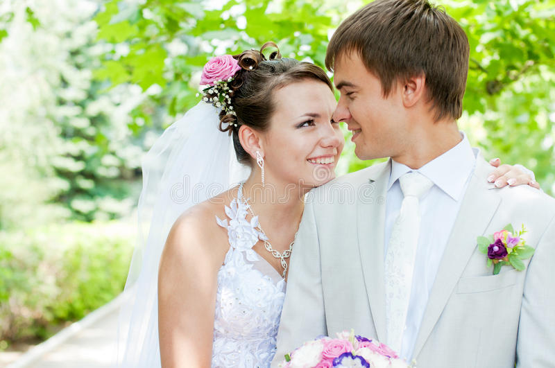 Young and beautiful bride and groom smiling at eac. Young bride and groom smiling at each othe royalty free stock photography