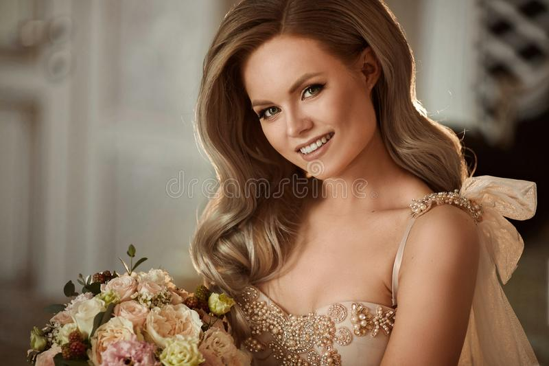 Young and beautiful bride, happy blonde model girl with gentle makeup and with wedding hairstyle in the stylish dress royalty free stock photo