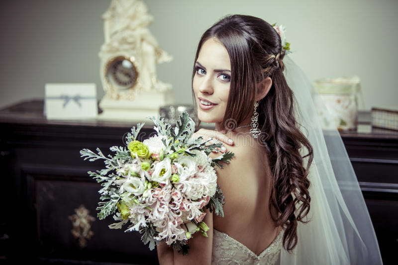 Young beautiful bride holding bouquet of flowers. royalty free stock photos
