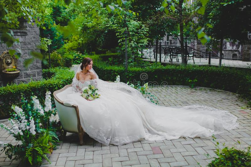 Young beautiful bride in luxury dress with a long train sitting on a sofa. On the territory of country hotel royalty free stock photo