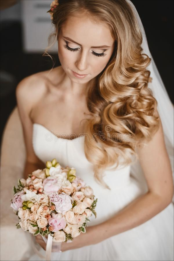 Young and beautiful bride, sensual blond model girl with gentle makeup and with wedding hairstyle in the white dress royalty free stock photos