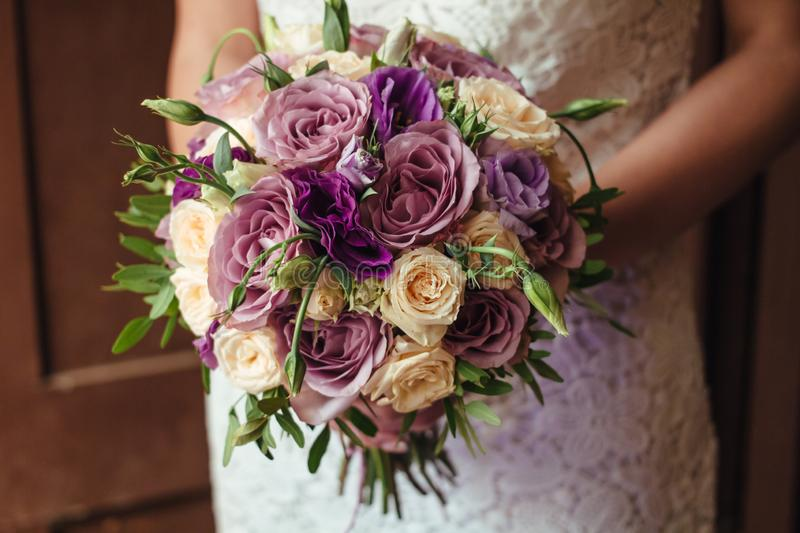 Young beautiful bride in white dress holding wedding bouquet, bouquet of bride from rose cream spray, rose bush, rose purple Memor. Y Lane, violet eustoma royalty free stock photo