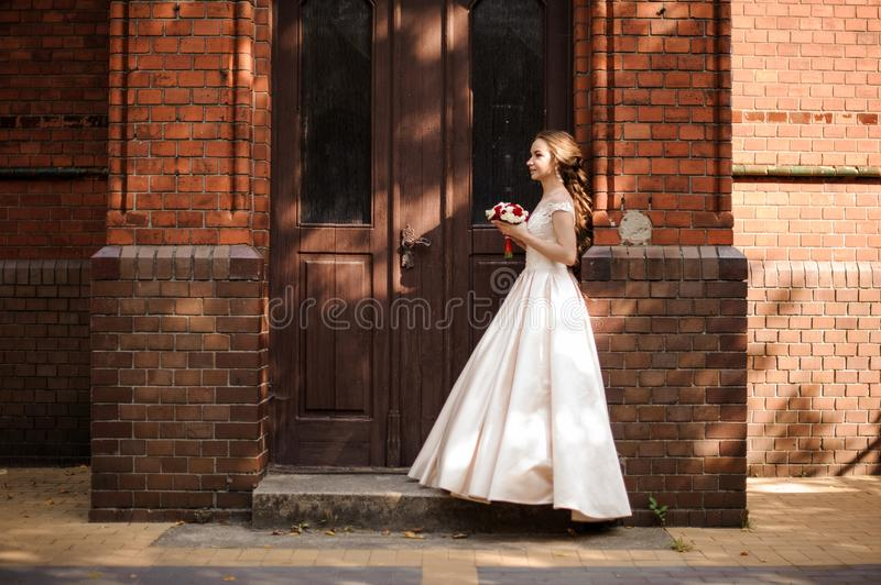 Young and beautiful bride in white wedding dress standing near the wooden door stock photography