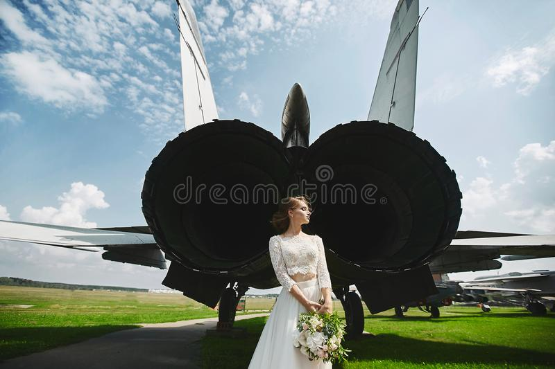 A young beautiful brown-haired bride is standing behind a jet plane royalty free stock images
