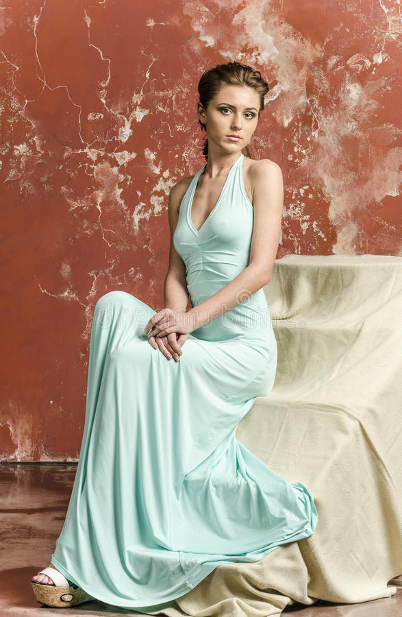 Young beautiful brown-haired woman in blue light silk dress with open shoulders and a long skirt and sandals stock images