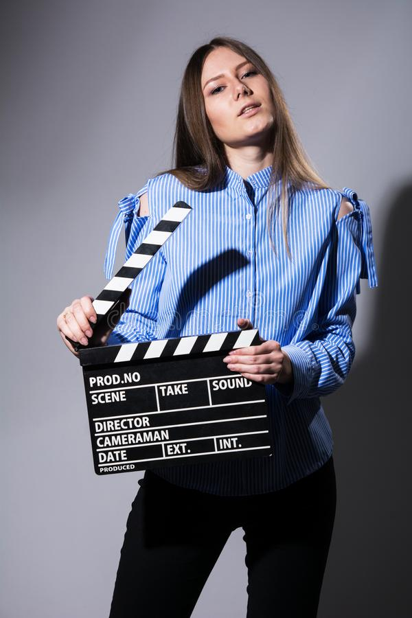 Young beautiful brown-haired woman with a movie cracker. Assistant director girl with long hair and striped shirt on a gray background stock photography