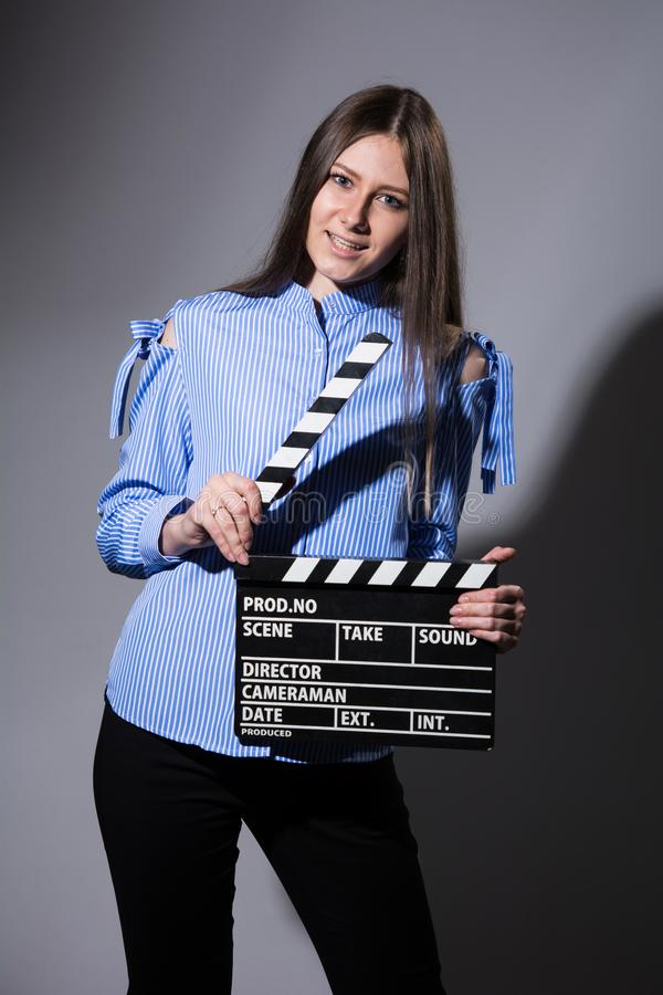 Young beautiful brown-haired woman with a movie cracker. Assistant director girl with long hair and striped shirt on a gray background royalty free stock photo