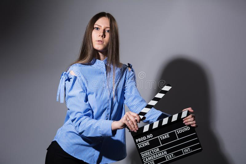 Young beautiful brown-haired woman with a movie cracker. Assistant director girl with long hair and striped shirt on a gray background royalty free stock image
