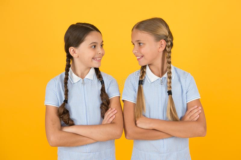 Young and beautiful. brunette and blond hair. sisterhood concept. best friends. vintage style. small girls in retro. Uniform. old school. back to school. happy stock photo