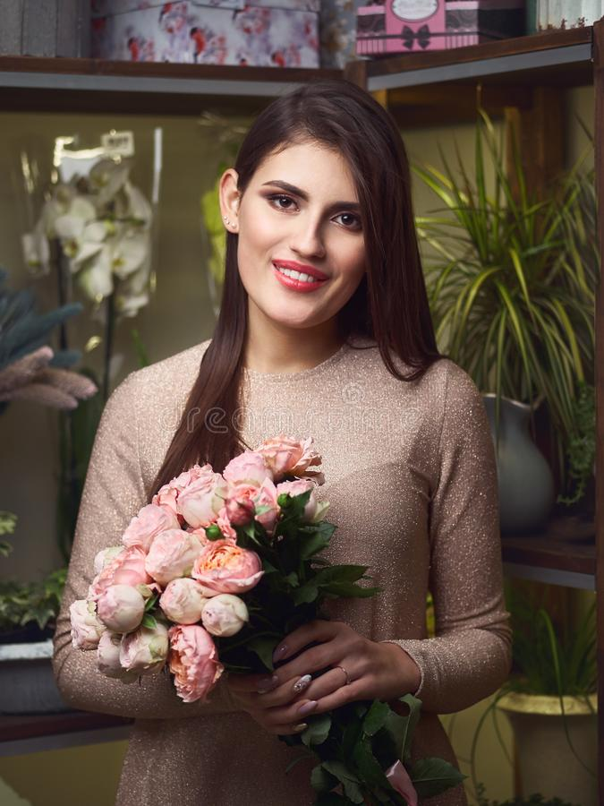 Young beautiful brunette business woman florist holding trendy bouquet of peony roses in flower shop stock photos