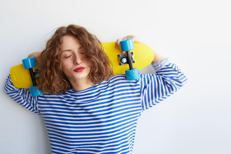 Young beautiful brunette female holding yellow skateboard stock images