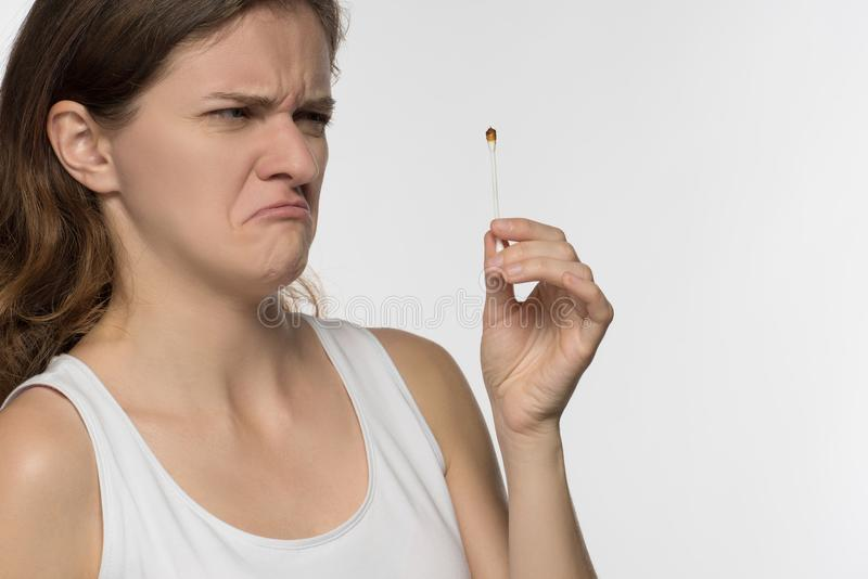 Young beautiful brunette girl cleans the ears with chopsticks wi stock photography