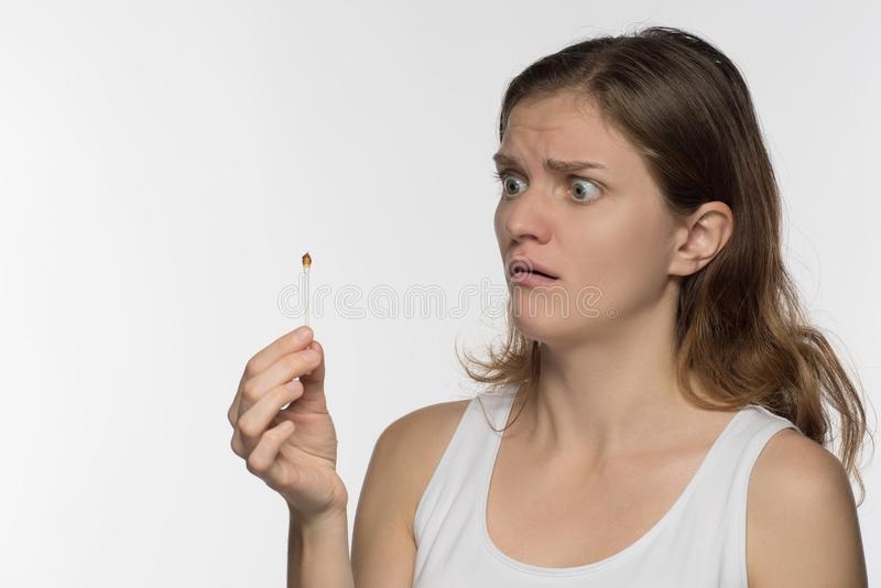 Young beautiful brunette girl cleans the ears with chopsticks wi stock photos