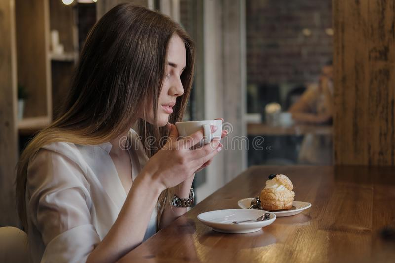 Young beautiful brunette girl in a loft style cafe sits at a table by the window, drinks coffee and eats a dessert cake. royalty free stock photos