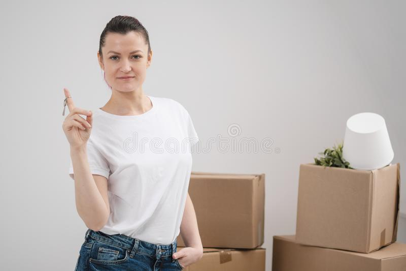 A young beautiful brunette girl in a white T-shirt holds in her hands the keys to a new home, against the background of royalty free stock photography