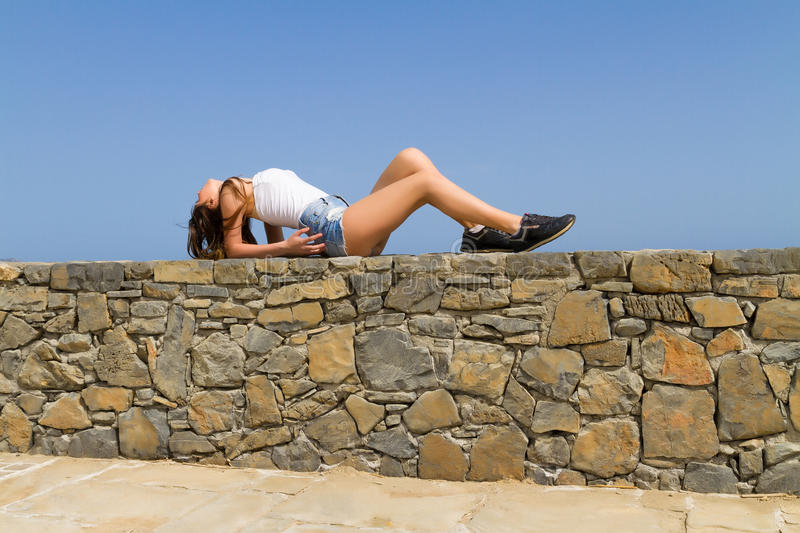 Young beautiful brunette in jean shorts enjoys the stock image
