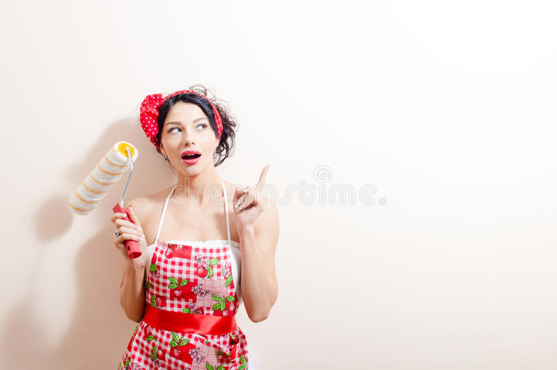 Young beautiful brunette lady in fun holding paint bolster & having refurbishing idea pointing with finger looking up. Picture of funny brunette pinup girl in royalty free stock photo